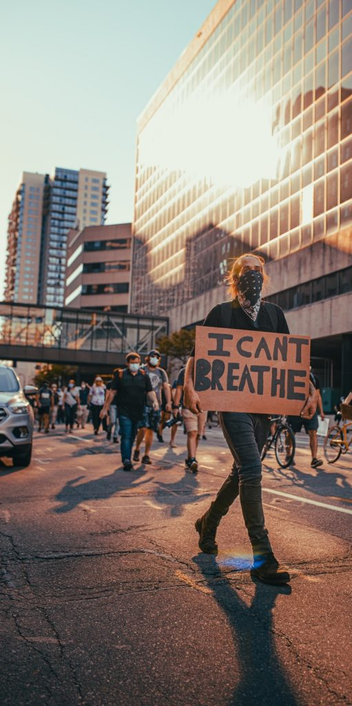 """Man wearing face mask holding sign saying """"I can't breathe"""" walking in protest march in city"""