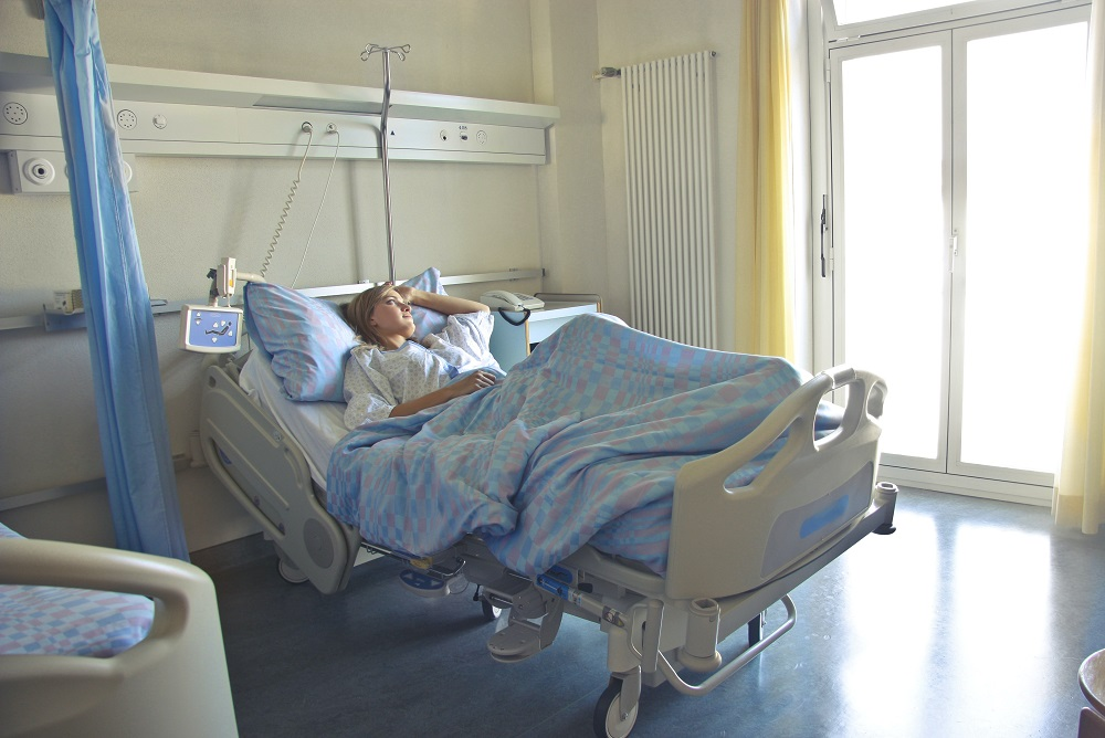 Woman who needs Power of Attorney (Medical) laying in brightly lit hospital room