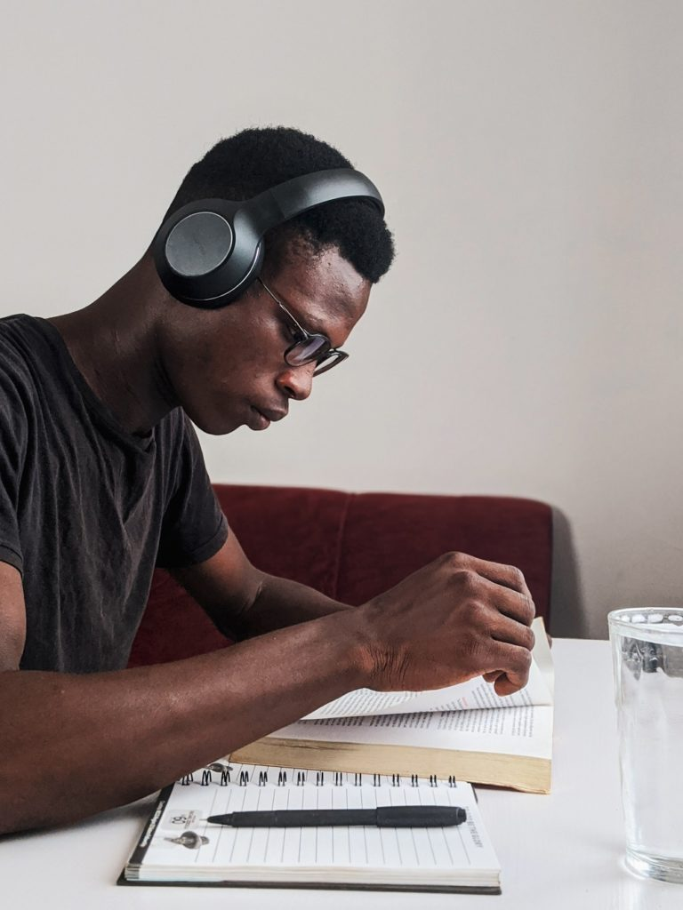 Man wearing headphones looking at student immigration paperwork